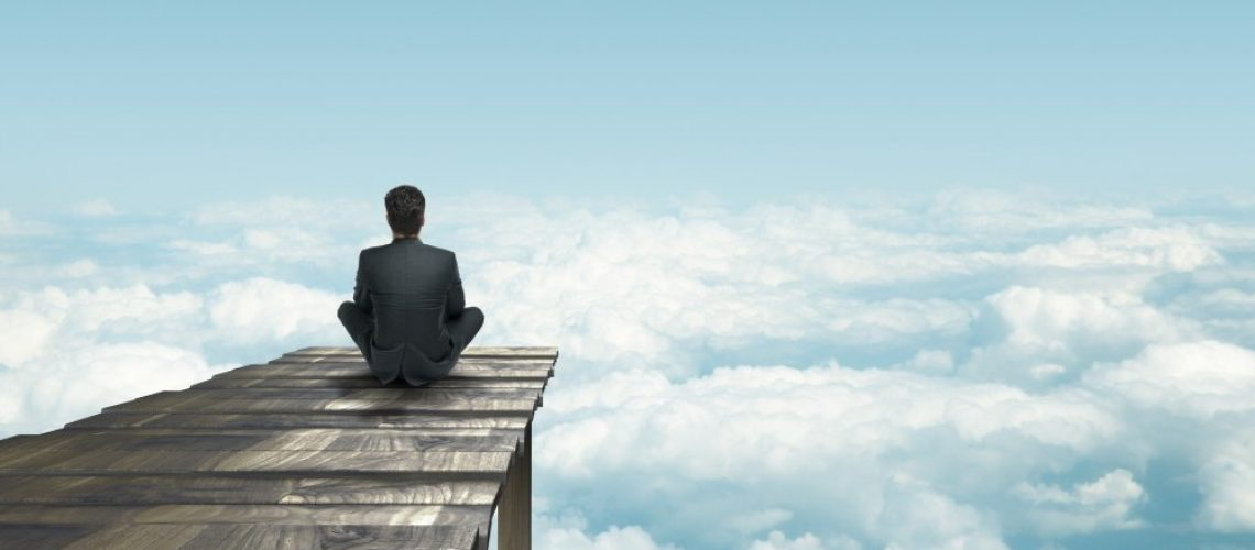 businessman sitting on pier an looking clouds